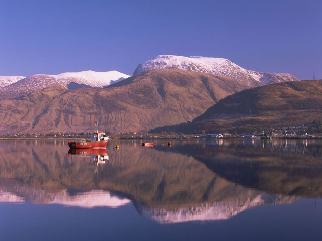 Looking across the calm waters of Loch Linnhe to Fort William and a snow duster Ben Nevis