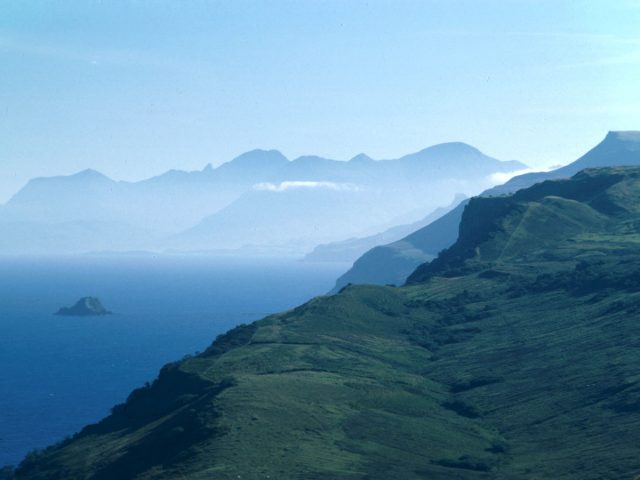 Looking along rugged coastline to mountains beyond, the Isle of Skye, The Highlands